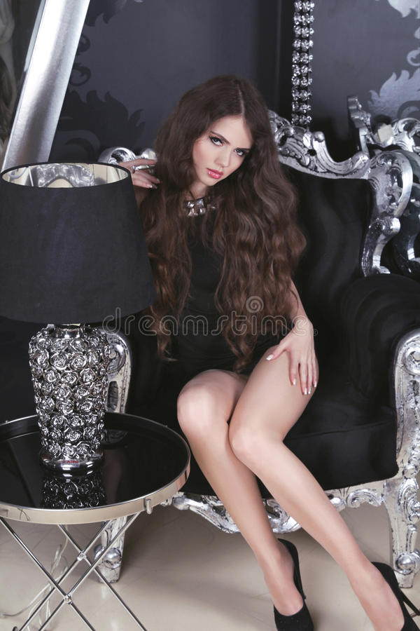 Beau modèle de fille de brune dans la robe noire courte posant sur le lux image stock