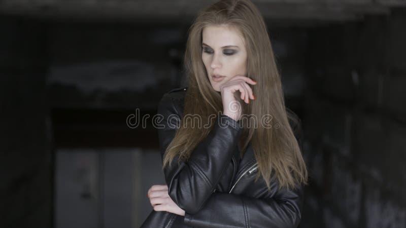 Beau modèle sexy à la mode posant dehors, touchant son visage, veste en cuir noire de port sur le fond noir images libres de droits