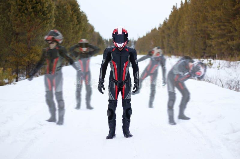 Beau motocycliste dans la pleins vitesse et casque Dans une forêt neigeuse d'hiver photo stock