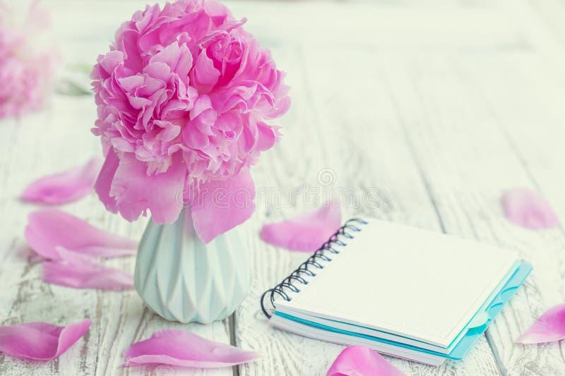 Beau pâlissez - le bouquet rose de pivoines dans le vase et le carnet vide au-dessus du fond blanc de table image libre de droits