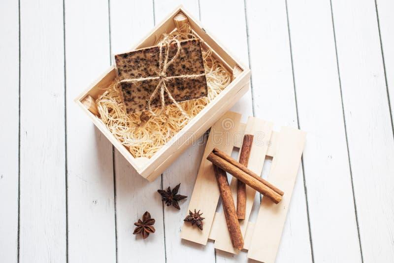 Beau, parfumé savon fait main avec des bâtons de cannelle d'anis d'étoile dans la position de boîte en bois sur un fond en bois photographie stock