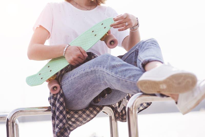 Beau patineur féminin de l'adolescence s'asseyant sur la rampe au parc de patin Concept des activités urbaines d'été image libre de droits