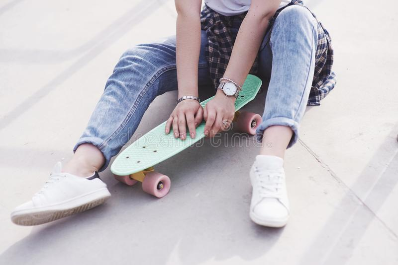 Beau patineur féminin de l'adolescence s'asseyant sur la rampe au parc de patin Concept des activités urbaines d'été photographie stock