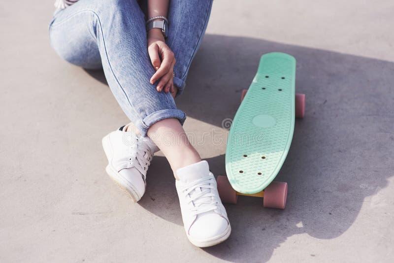 Beau patineur féminin de l'adolescence s'asseyant sur la rampe au parc de patin Concept des activités urbaines d'été images stock