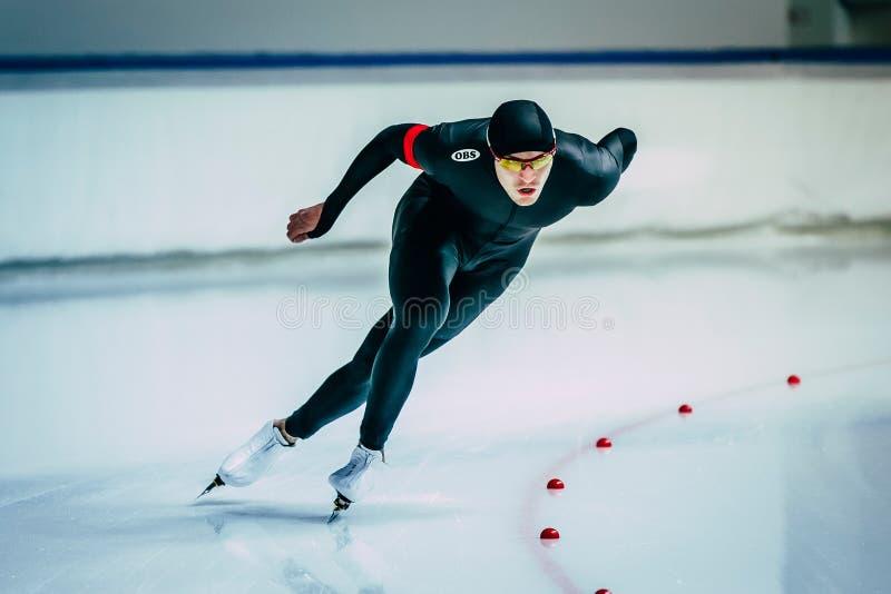 Beau patineur masculin pendant la distance de sprint de course le long du chemin du palais de glace photos stock