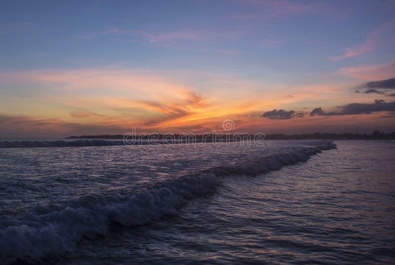 Beau paysage étonnant de la plage tropicale sous le ciel orange de coucher du soleil à la baie de Weligama photos libres de droits