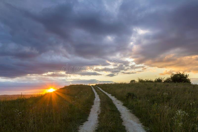 Beau paysage au coucher du soleil ou lever de soleil, route moulue étroite s'étendant par le pré de floraison herbeux vert au Li  photos libres de droits