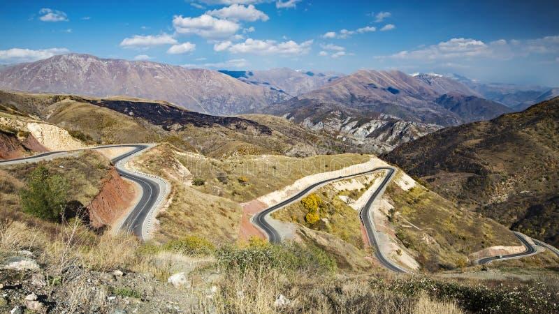 Beau paysage avec la longue route rurale menant par des collines photos stock