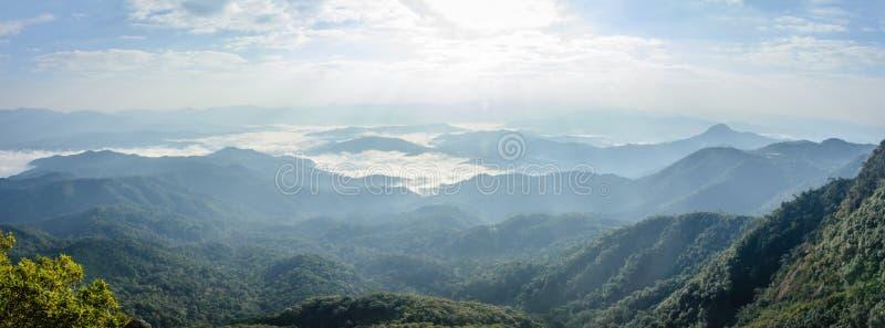 Beau paysage avec le ciel nuageux, mer nuageuse, soleil, mountai photographie stock libre de droits