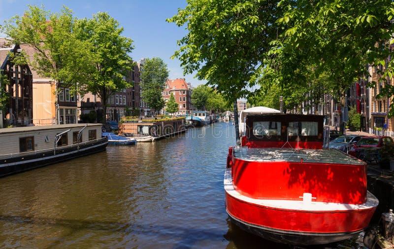 Beau paysage avec les maisons et les bateaux médiévaux sur le canal à Amsterdam photographie stock