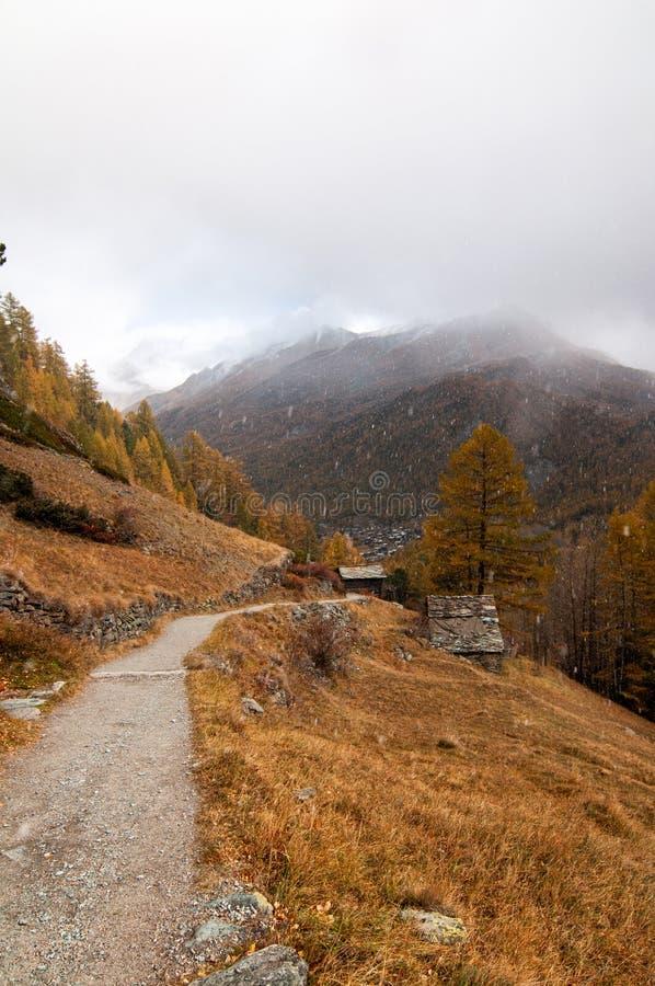Beau paysage d'automne avec la neige tombant au-dessus d'un chemin vers la station de vacances de Zermatt images libres de droits