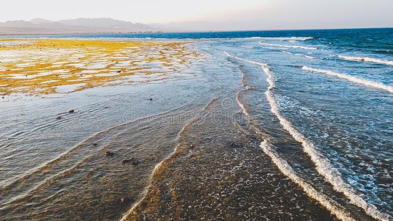 Beau paysage d'océan calme et des montagnes sur les vagues de mer de côte roulant et freinant au-dessus du récif coralien mort et photos libres de droits