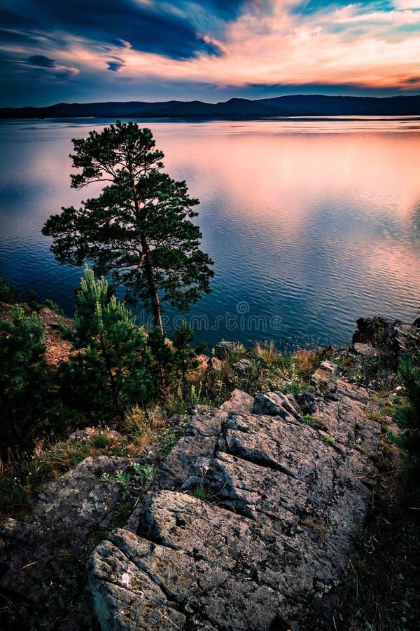 Beau paysage de coucher du soleil sur le lac de montagne avec les roches et le pin photos stock