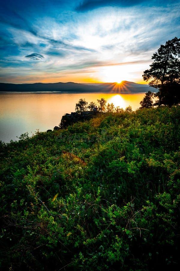 Beau paysage de coucher du soleil sur le lac de montagne avec le soleil se cachant derrière les montagnes photos libres de droits