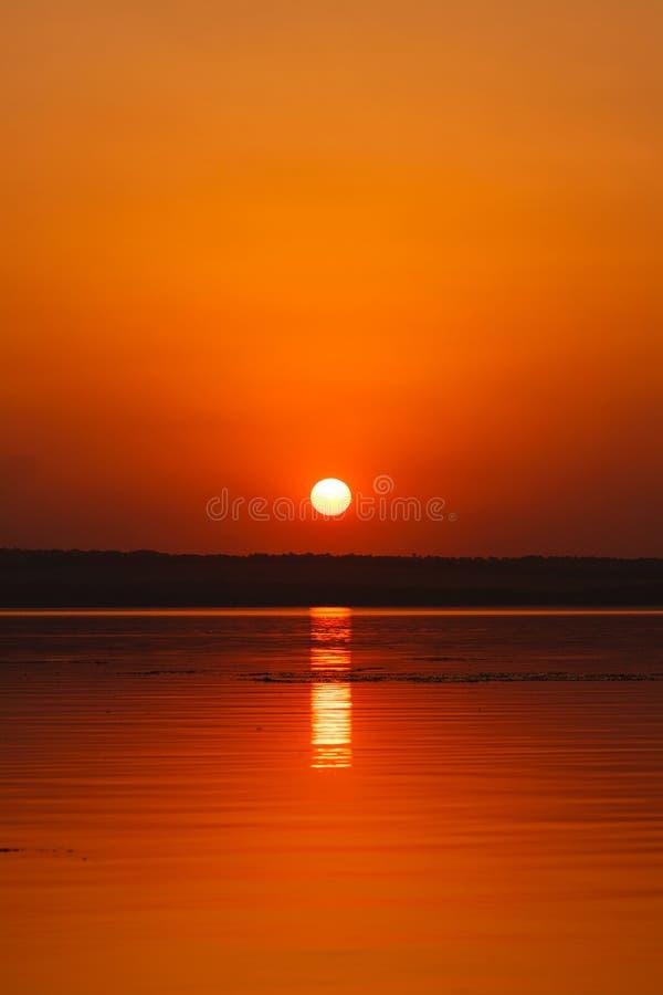 Beau paysage de flambage de coucher du soleil à la rivière Dnipro et au ciel orange au-dessus de lui avec la réflexion d'or du so photos stock