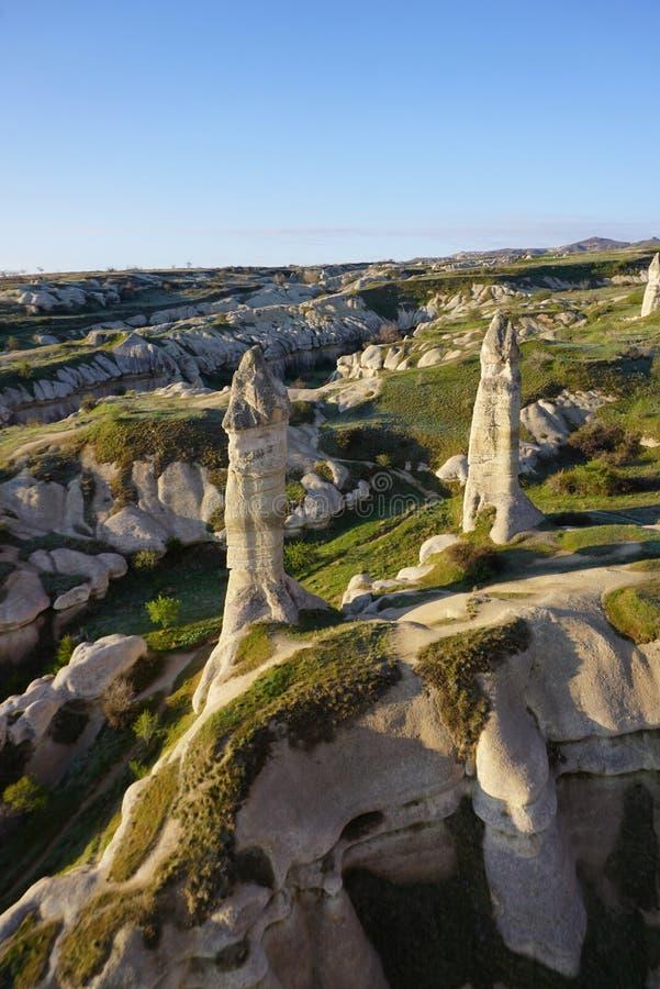 Beau paysage de Goreme avec la flèche mince de cheminée féerique de la roche qui dépasse du fond image stock