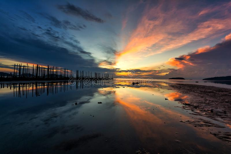 Beau paysage de lever de soleil au ciel bleu et orange au-dessus de lui avec la réflexion de la lumière sur la mer images libres de droits