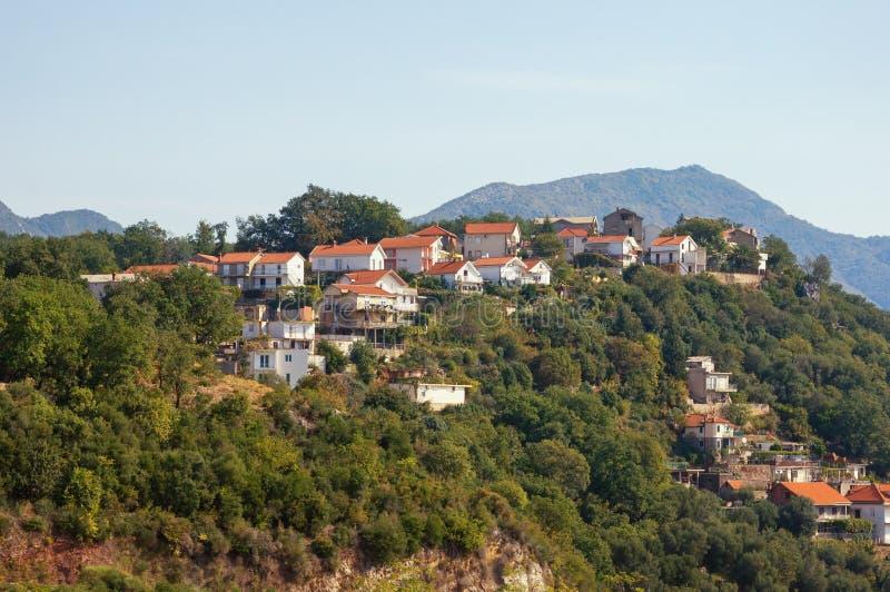 Beau paysage de montagne avec des maisons avec les toits rouges sur le flanc de montagne Monténégro, Herceg Novi photo stock