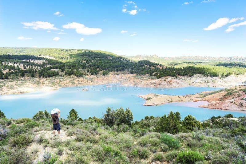 Beau paysage de montagne avec un lac, un homme dans un chapeau de paille avec une caméra image libre de droits