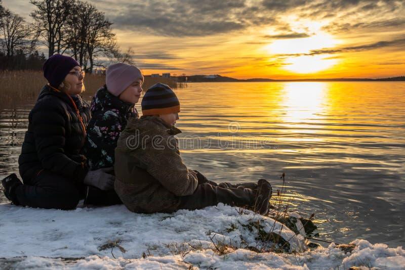 Beau paysage orange d'hiver par la mer avec une femme et des enfants s'asseyant dans la neige sur une roche regardant un Re lumin photographie stock libre de droits