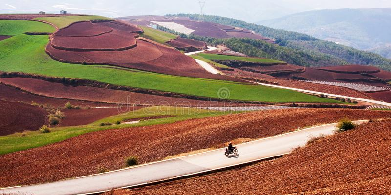 Beau paysage rural dans le sud de la Chine, terre rouge de Dongchuan Hommes chinois locaux montant la moto sur la route goudronné photos stock