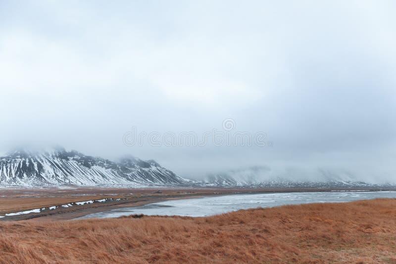 beau paysage scénique avec le pré, le fjord et couvert de neige herbeux image libre de droits