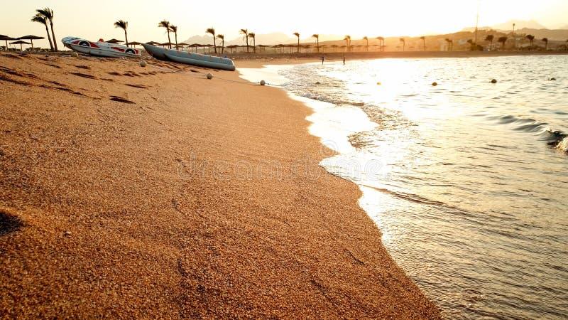 Beau paysage stupéfiant de coucher du soleil au-dessus des vagues de mer calme et de la plage arénacée d'océan photo stock