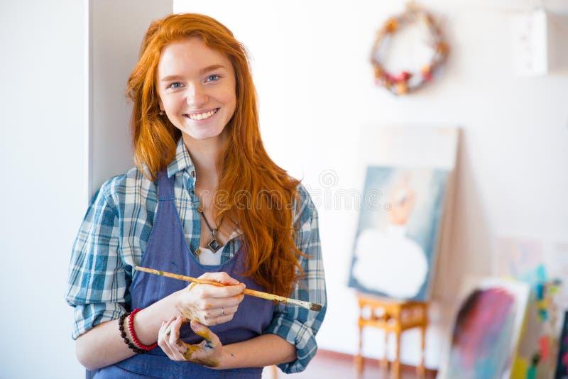 Beau peintre gai de femme avec la longue brosse rouge de participation de cheveux image stock