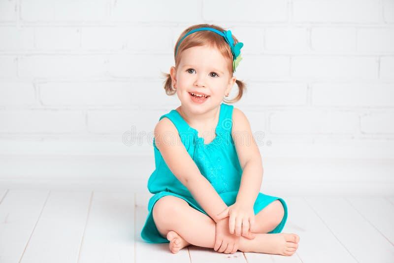 Beau petit bébé dans une robe de turquoise image libre de droits