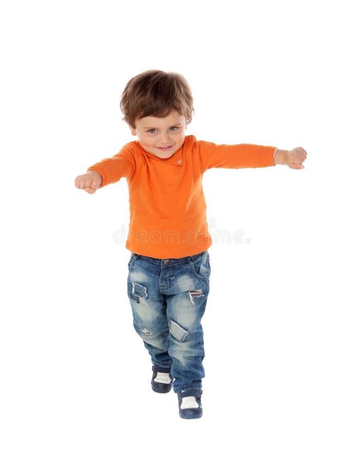 Beau petit enfant deux années portant les jeans et le je orange image stock