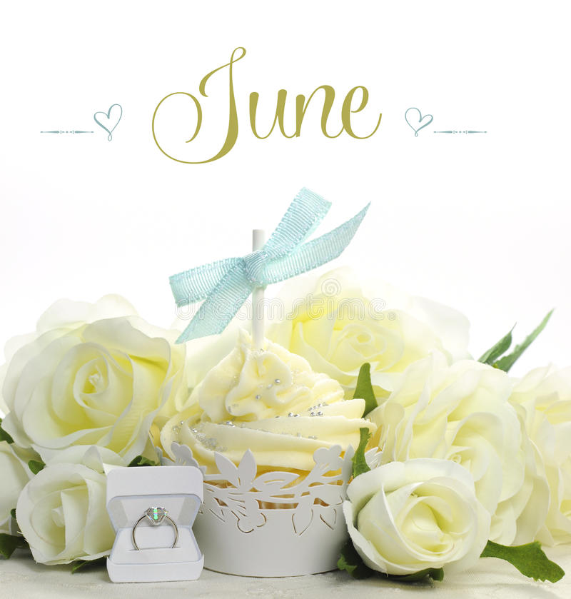 Beau petit gâteau blanc de thème de jeune mariée de juin avec les fleurs et les décorations saisonnières pour le mois de juin images stock