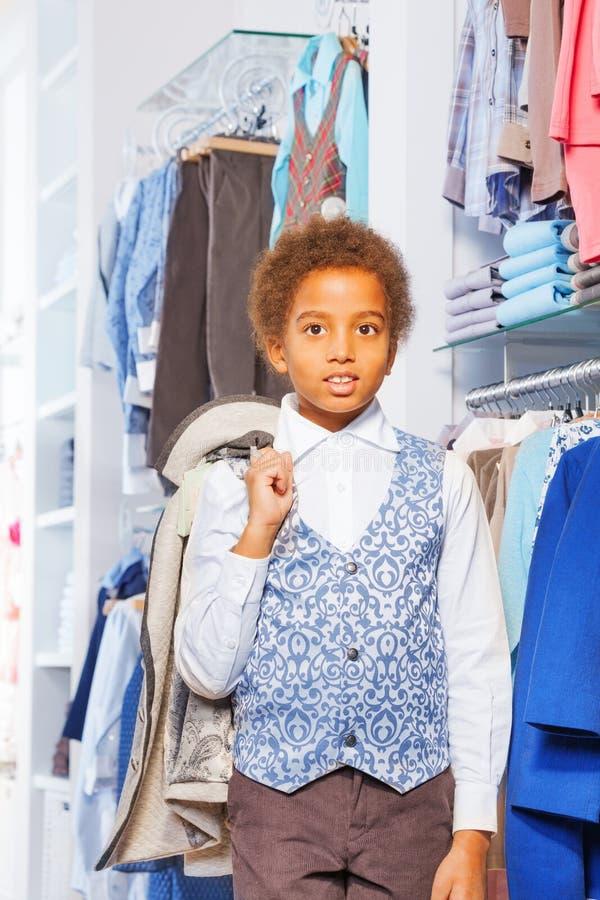 Beau petit garçon africain tenant la veste dans la boutique image stock