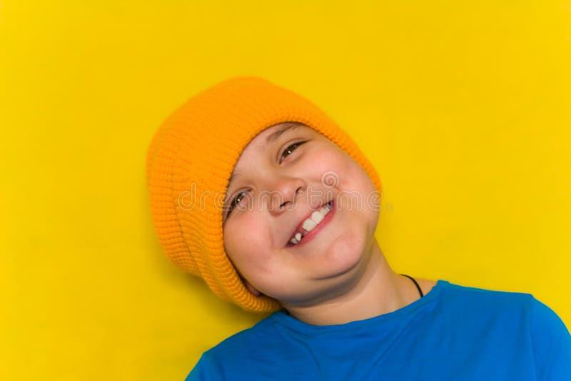 beau petit gar?on dans le chapeau jaune et la chemise bleue d'isolement au-dessus du fond jaune photos libres de droits