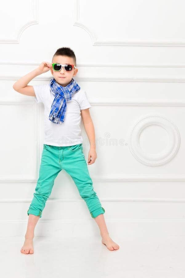 Beau petit gar?on de mode dans le pantalon et le T-shirt et l'?charpe lumineux photo stock