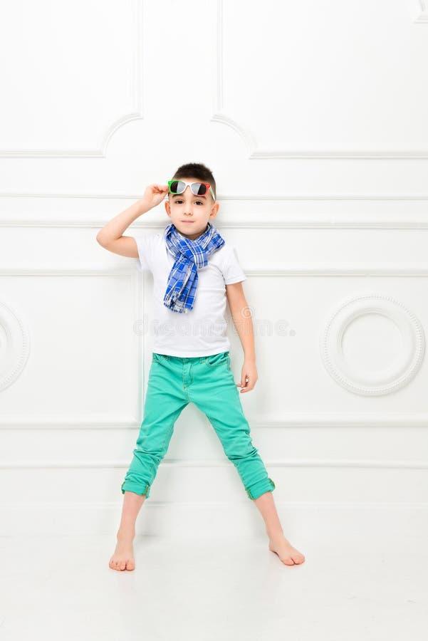 Beau petit gar?on de mode dans le pantalon et le T-shirt et l'?charpe lumineux photos libres de droits