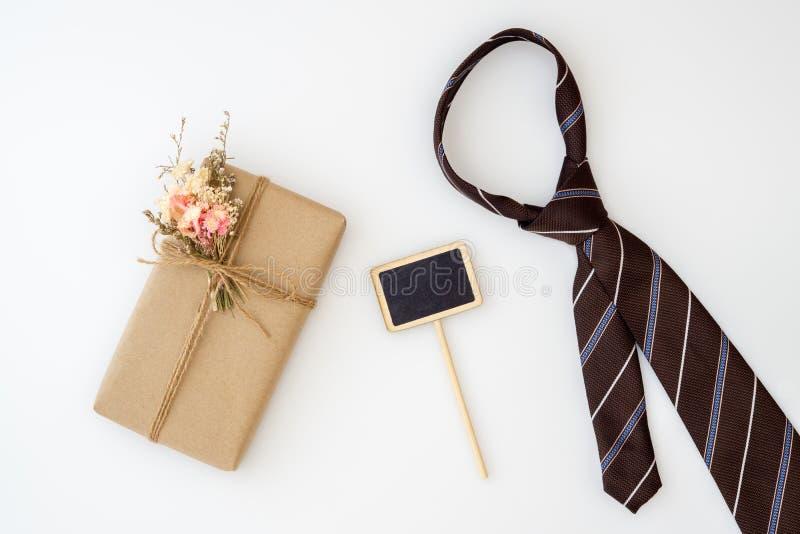 Beau petit paquet fait main de boîte-cadeau de DIY avec les fleurs et la corde décorative, la cravate du père et le petit tableau images stock