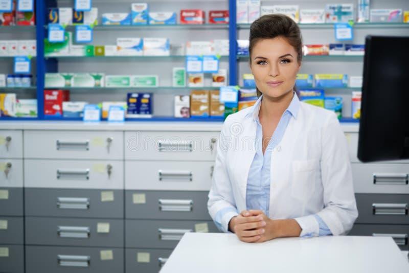Beau pharmacien de sourire de jeune femme faisant le sien travail dans la pharmacie photo libre de droits