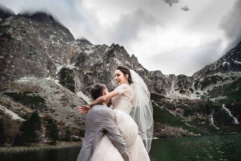 Beau photosession l'?pousant Le mari? entoure sa jeune jeune mari?e, sur le rivage du lac Morskie Oko poland images stock