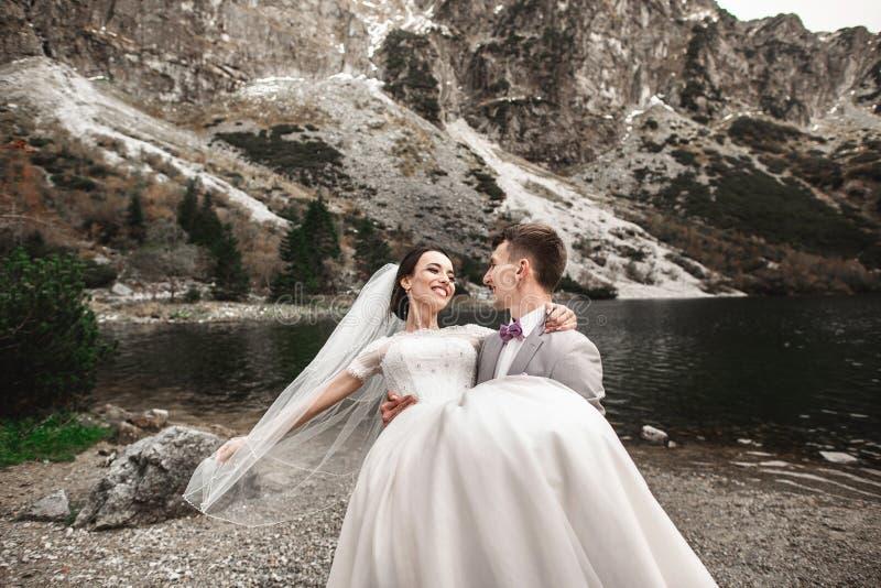 Beau photosession l'?pousant Le mari? entoure sa jeune jeune mari?e, sur le rivage du lac Morskie Oko poland photographie stock libre de droits