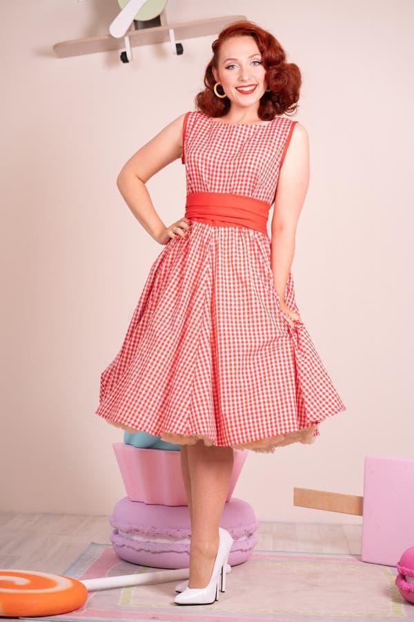 Beau pin-up roux souriant heureusement fille posant dans une rétro robe rouge et des talons hauts blancs photo libre de droits