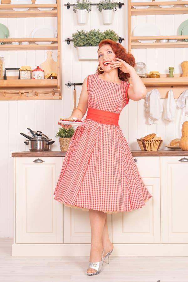 Beau pin-up roux souriant heureusement fille posant dans une rétro robe rouge et des talons hauts blancs image libre de droits