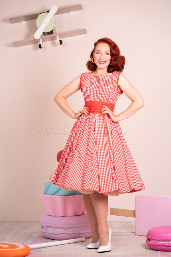 Beau pin-up roux souriant heureusement fille posant dans une rétro robe rouge et des talons hauts blancs photos stock