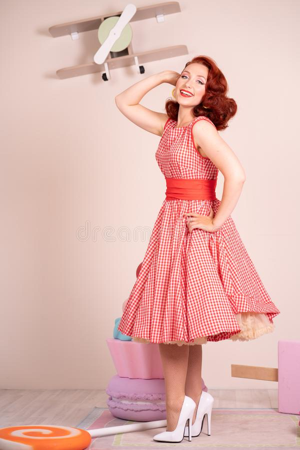 Beau pin-up roux souriant heureusement fille posant dans une rétro robe rouge et des talons hauts blancs photographie stock libre de droits