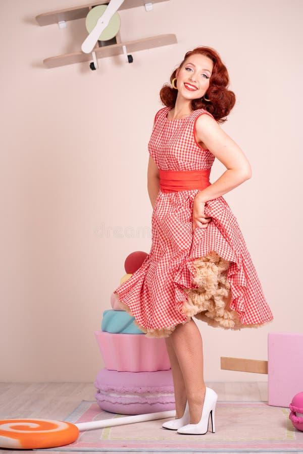Beau pin-up roux souriant heureusement fille posant dans une rétro robe rouge et des talons hauts blancs image stock