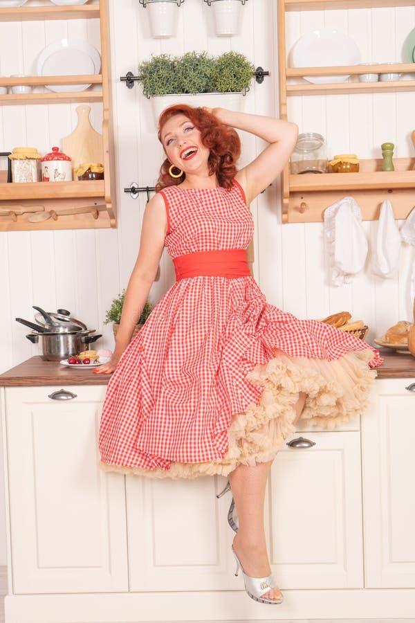 Beau pin-up roux souriant heureusement fille posant dans une rétro robe rouge et des talons hauts blancs images stock