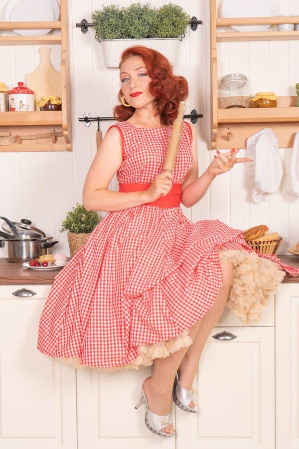 Beau pin-up roux souriant heureusement fille posant dans une rétro robe rouge dans seule la cuisine photos libres de droits