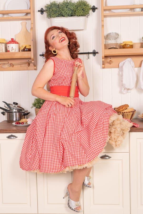 Beau pin-up roux souriant heureusement fille posant dans une rétro robe rouge dans seule la cuisine images libres de droits