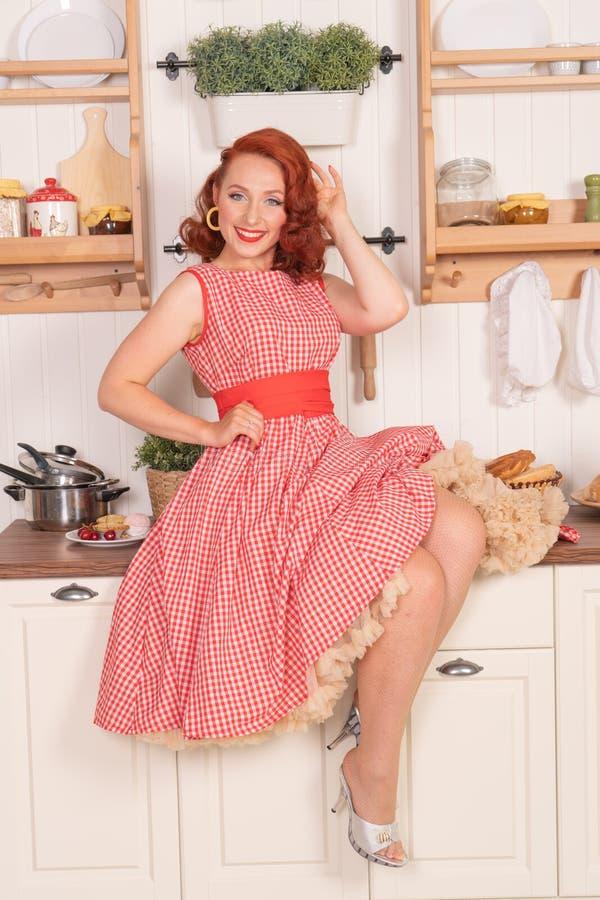 Beau pin-up roux souriant heureusement fille posant dans une rétro robe rouge dans seule la cuisine photographie stock libre de droits