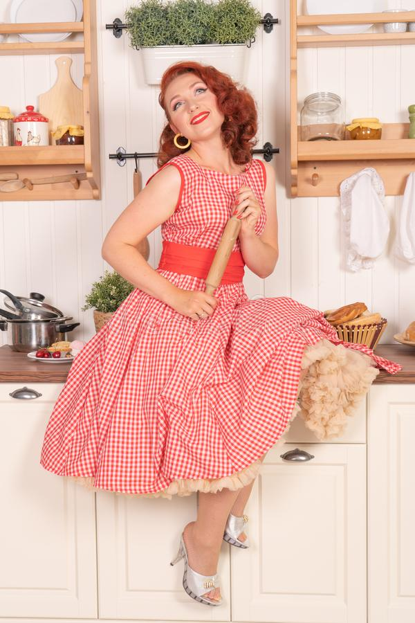 Beau pin-up roux souriant heureusement fille posant dans une rétro robe rouge dans seule la cuisine photo libre de droits