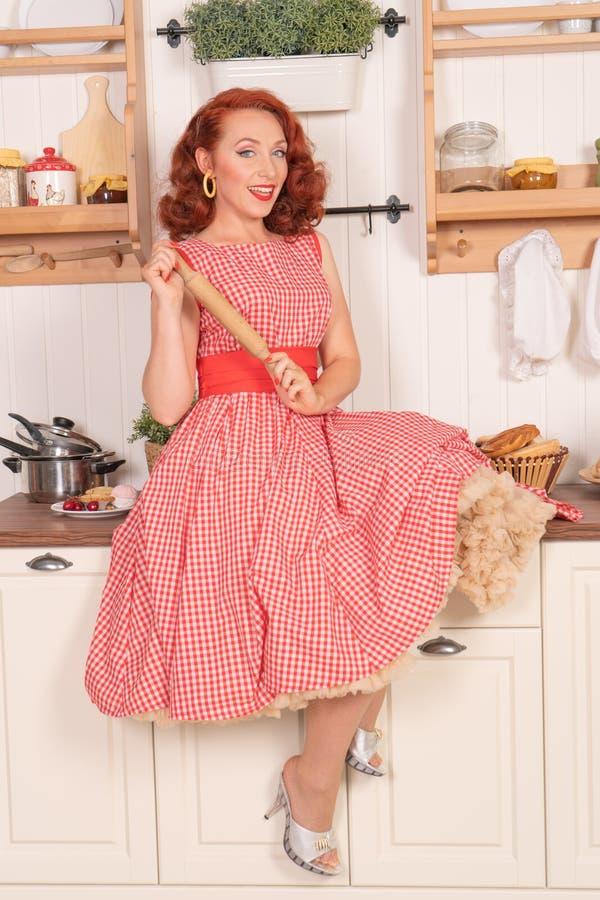 Beau pin-up roux souriant heureusement fille posant dans une rétro robe rouge dans seule la cuisine photo stock